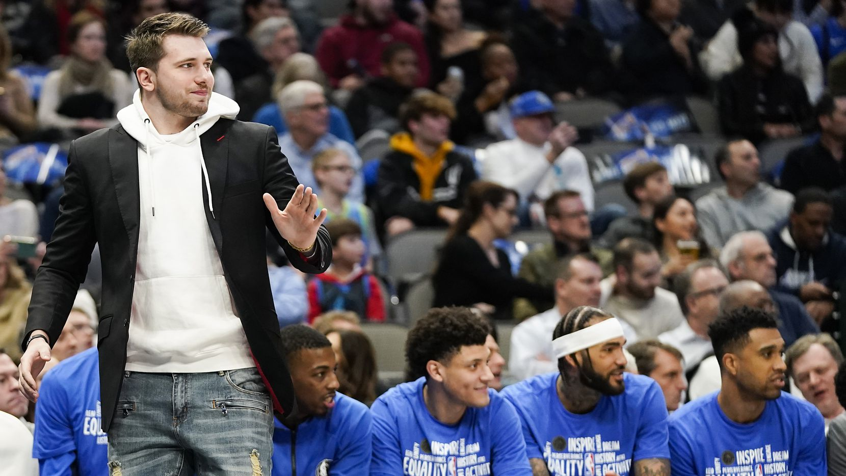 Injured Dallas Mavericks guard Luka Doncic watches from the sidelines in street clothes during the first half of an NBA basketball game against the Memphis Grizzlies at American Airlines Center on Wednesday, Feb. 5, 2020, in Dallas.