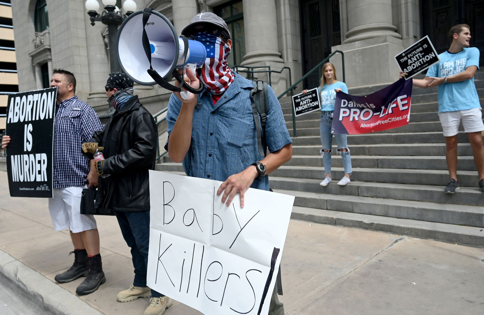 Daniel Lee, wielding a bullhorn in front of the Dallas Municipal Building, was among counter-protesters who let abortion-rights demonstrators know their views on the issue.