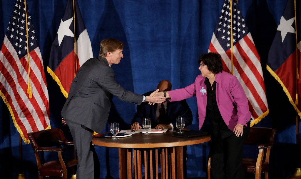 Texas Democratic gubernatorial candidates Andrew White (left) and Lupe Valdez (right) shake hands following their debate on May 11, 2018, in Austin ahead of the state's May 22 primary runoff election. Moderator Gromer Jeffers is at center.