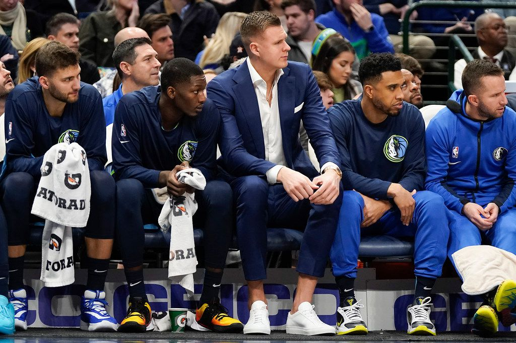 Injured Dallas Mavericks forward Kristaps Porzingis watches from the bench during the first half of an NBA basketball game against the Philadelphia 76ers at American Airlines Center on Saturday, Jan. 11, 2020, in Dallas.