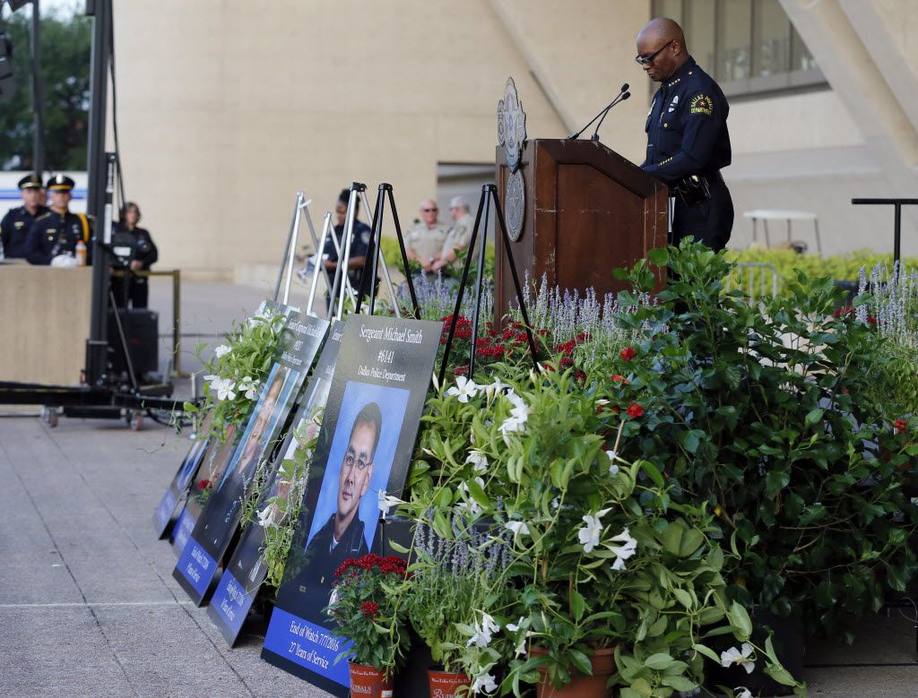 Friends and family fallen police officers arrive for a candlelight vigil at City Hall, Monday, July 11, 2016, in Dallas. Five police officers were killed and several injured during a shooting in downtown Dallas last Thursday night. (AP Photo/Tony Gutierrez)