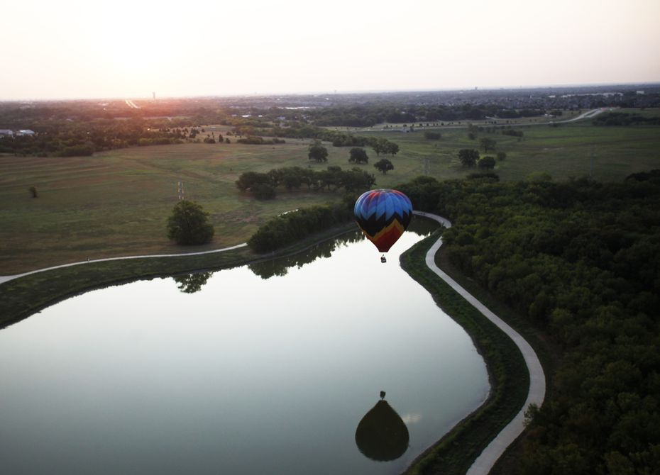 A balloon touches down over the water during a media flight before the Plano Balloon Festival  at Oak Point Park.