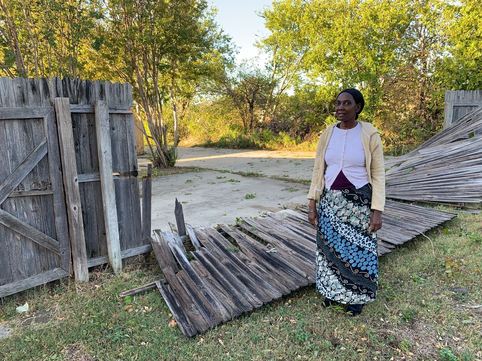 Mary Francis stands in front of a collapsed fence on October 21, 2019, in her backyard. She lives in Dallas just south of Buckingham Road, the street that divides Dallas and Richardson. She thanked God that she only suffered property damage in Sunday night's tornado. A tree collapsed in her front yard, a cover over her back patio shattered and fences on two sides of her backyard were damaged. The damage was worse in Richardson, just north of her home.