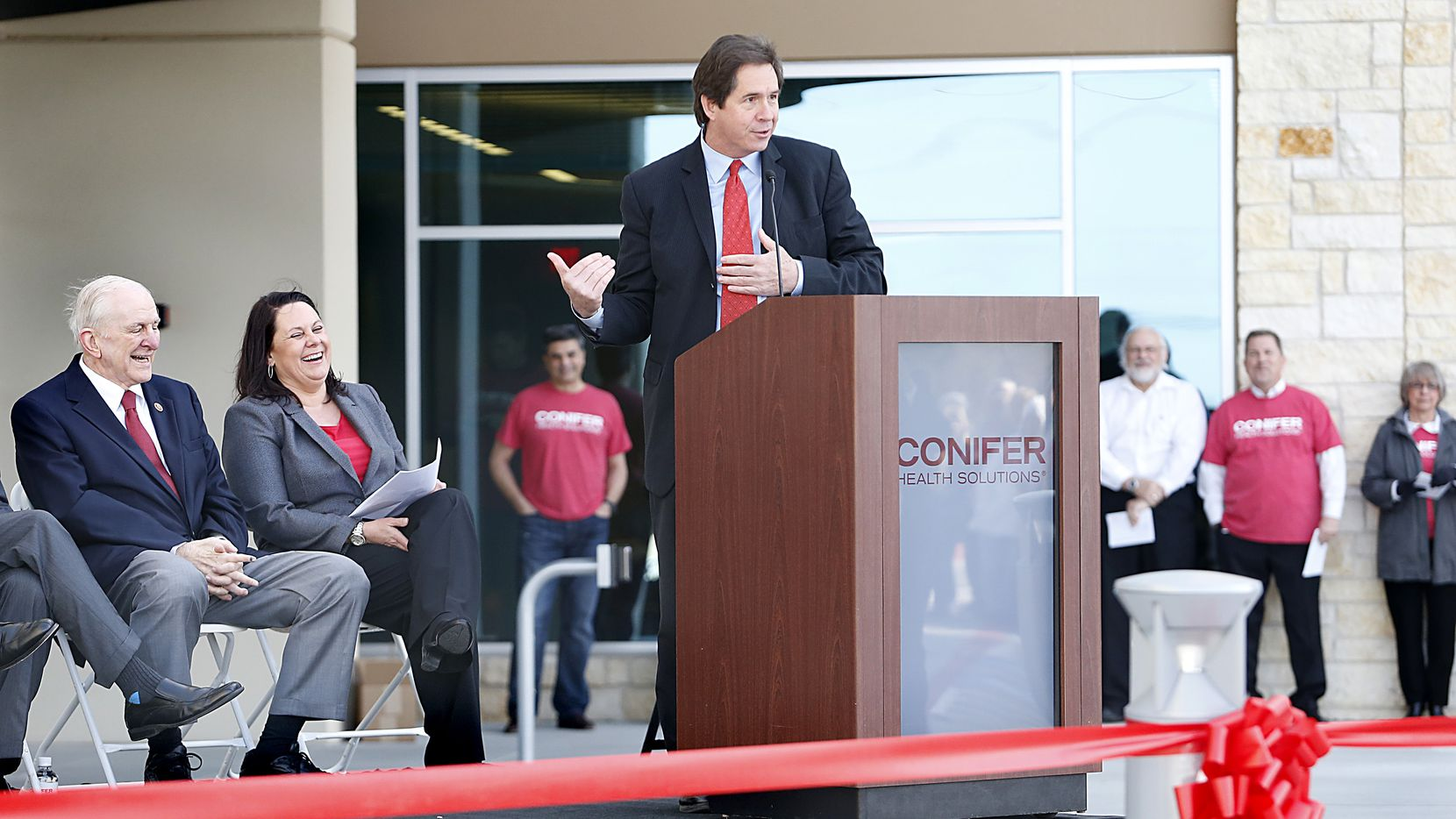 Tony Felker (center), president of the Frisco Chamber of Commerce speaks during a ribbon cutting ceremony for Conifer Health Solutions new building in Frisco.