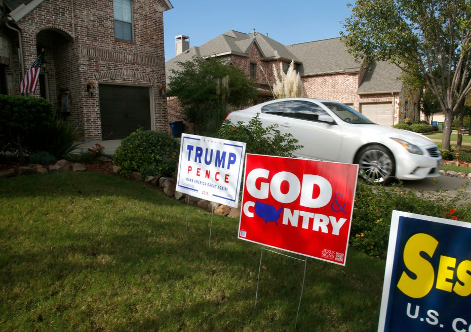 Riner pulls out of her drive past political signs supporting Donald Trump and Pete Sessions as she leaves her home office to go show a property to a potential tenant in Sachse, Texas.