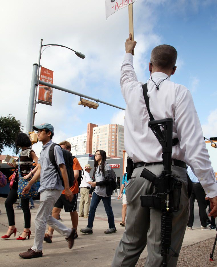 Andrew Clements (right), a licensed gun owner, open carrying a high-velocity rifle, demonstrates on Guadalupe Street next to the University of Texas in Austin on Wednesday Aug. 24, 2016, as a group of students carries sex toys to protest the campus concealed carry law, which went into effect in August. (AP Photo/John Mone)