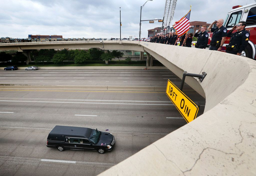 Richardson firefighters and police officers salute as the body of slain Dallas Police Officer Rogelio Santander passes them during a funeral procession on North Central Expressway and Galatyn Parkway in Richardson, Texas on Tuesday, May 1, 2018. Santander was shot and killed a week earlier while trying to arrest a man at a Home Depot.