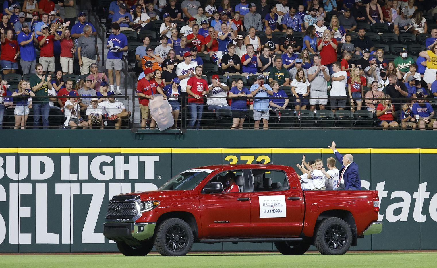 Texas Rangers executive vice president and public address announcer Chuck Morgan (right, in bed of truck) waves to fans following his induction into the Texas Rangers Baseball Hall of Fame at Globe Life Field in Arlington, Saturday, August 14, 2021.(Tom Fox/The Dallas Morning News)