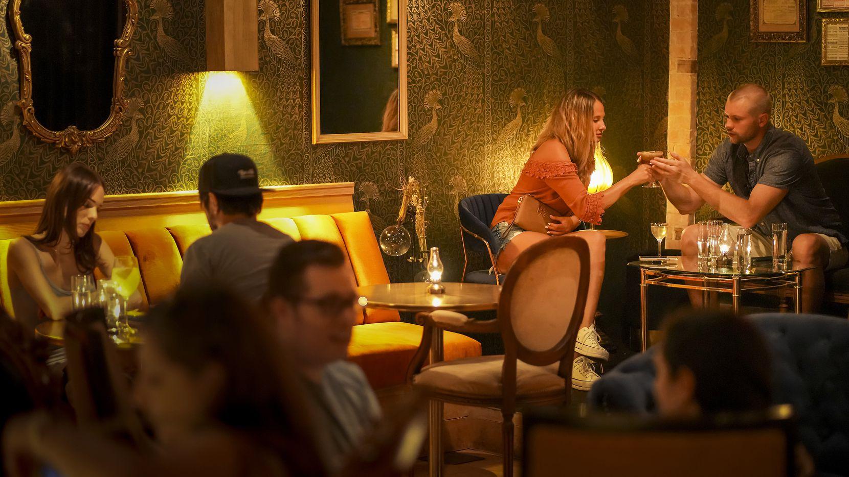 Heather Lustig y Jack Beale (atrás) comparten una bebida en Apothecary, un nuevo bar en Lowest Greenville, el 8 de julio de 2021 en Dallas.