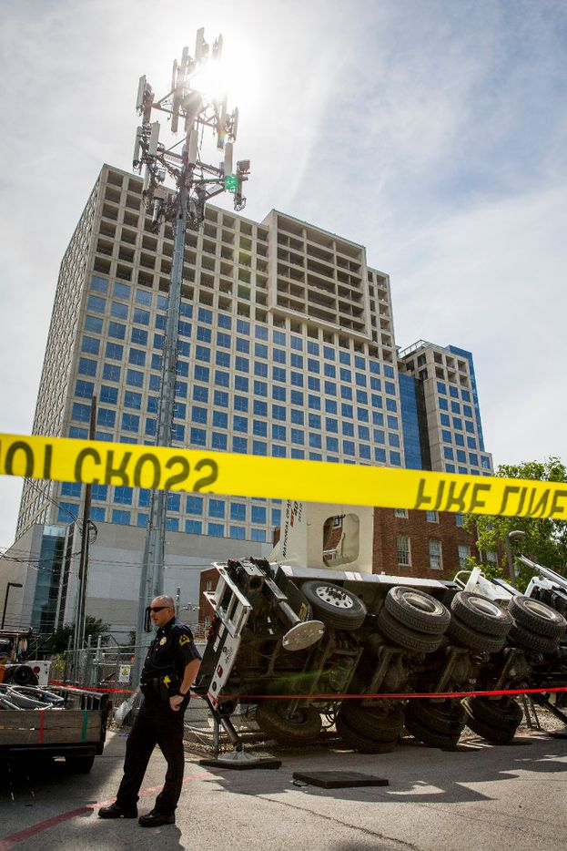 A Dallas police officer stands at the scene of an incident at 1700 Arts Plaza (near Ross Ave. and Flora Street) where a crane accident resulted in a fatality on Monday, April 24, 2017, in Dallas.  One person was killed, one was transported to the hospital with injuries that were not life-threatening and one person was treated and released at the scene. (Smiley N. Pool/The Dallas Morning News)