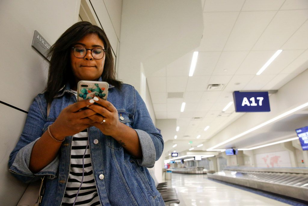 Nicole Gilmore of Washington D.C. flew out of Reagan International Airport and had connecting flight out of DFW Airport to College Station for a workshop when her connecting flight was cancelled on Wednesday, April 17, 2019. She was propped up against a wall so she could power her phone and try to figure out if she could get a flight on Thursday morning.  (Brian Elledge/The Dallas Morning News)