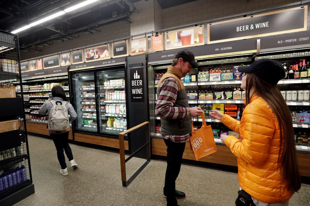 In this Jan. 22, 2018, file photo, a worker, right, looks at the ID of a shopper at the wine and beer area inside an Amazon Go store in Seattle.