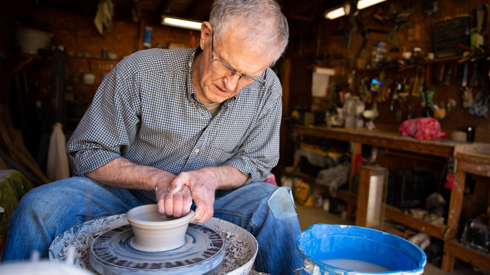 Bill Reed, a 74-year-old retiree, shapes a clay bowl in his garage workshop in Denton.