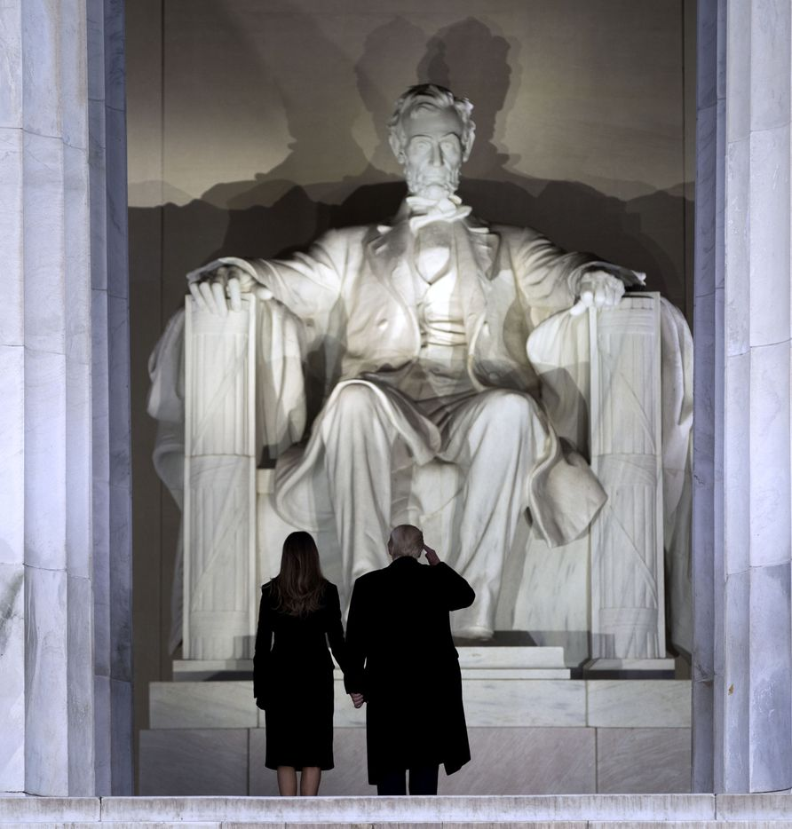 President-elect Donald Trump salutes Abraham Lincoln before he and his wife, Melania, descend the steps of the Lincoln Memorial to a welcome concert on the day before his inauguration in Washington, Jan. 19, 2017.