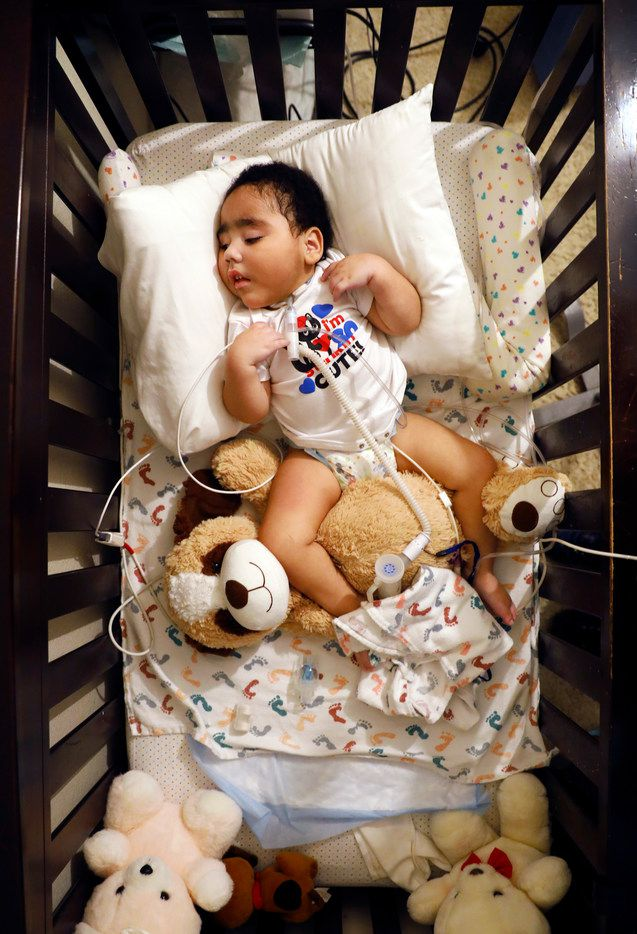 D'ashon Morris, who is in a vegetative state, rests in his crib as he receives his breakfast before visual stimulation therapy at his Mesquite, Texas home, Tuesday, March 6, 2018.