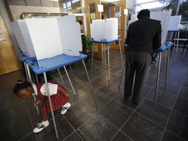 Christiana Adesanya, 6, plays around the voting area while her mother Christine Adesanya, right, of Irving, filling out her ballot at Jack E. Singley Academy in Irving on Nov. 6, 2012.