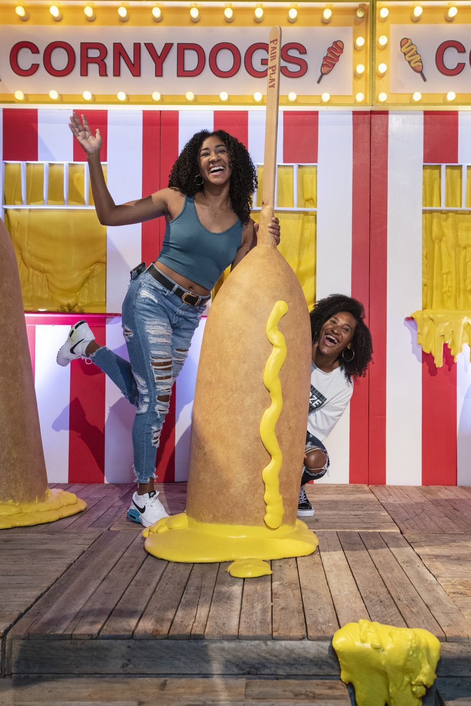 Victoria Roberts, left, and Anastatia Harrison, pose for photos with gigantic corny dogs at one of the photobooth-like displays at the State Fair themed installation titled Fair Play at The Statler in downtown Dallas.