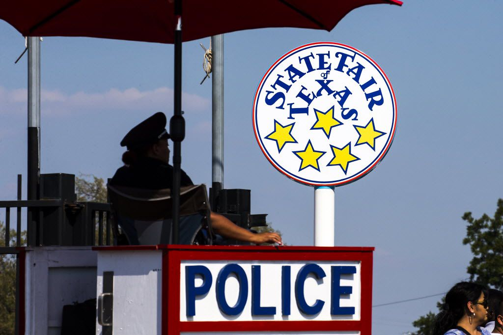 A Dallas police officer keeps watch over an entrance gate during the opening weekend of the 2015 State Fair of Texas.