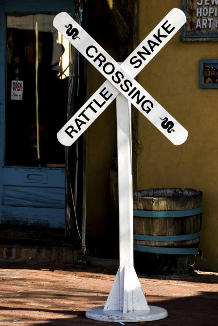 """A """"Rattlesnake Crossing"""" sign sits outside the American International Rattlesnake Museum.  This buzzing place lies in Albuquerque's Old Town, an enclave of historic structures built around the three-century-old San Felipe de Neri Parish church."""
