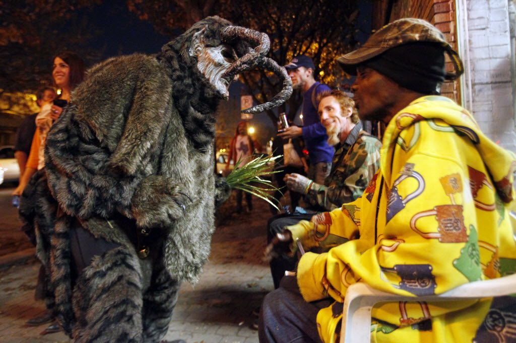 A Krampus character asks a man if he knows what a Krampus does to people who misbehave, during the Dallas Krampus Walk through the streets of Deep Ellum, organized by the Krampus Society and Dark Hour Haunted House, on Friday, Dec. 5, 2014.