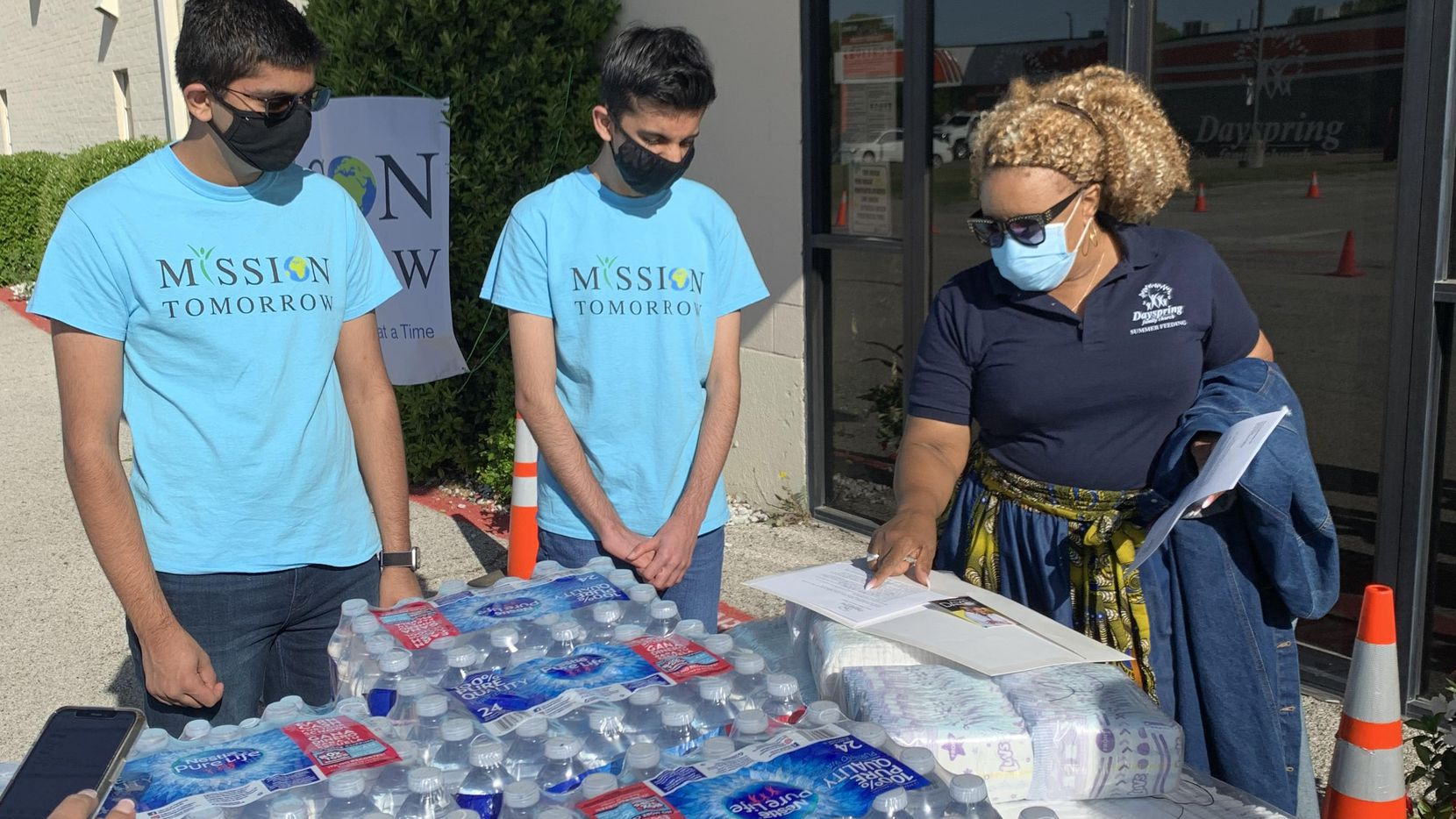 Mission Tomorrow co-founders Vansh (from left) and Dhruv Nanda work with pastor Sonjia Dickerson to help distribute 8,000 bottles of water at Dayspring Family Church Food Pantry in Irving.