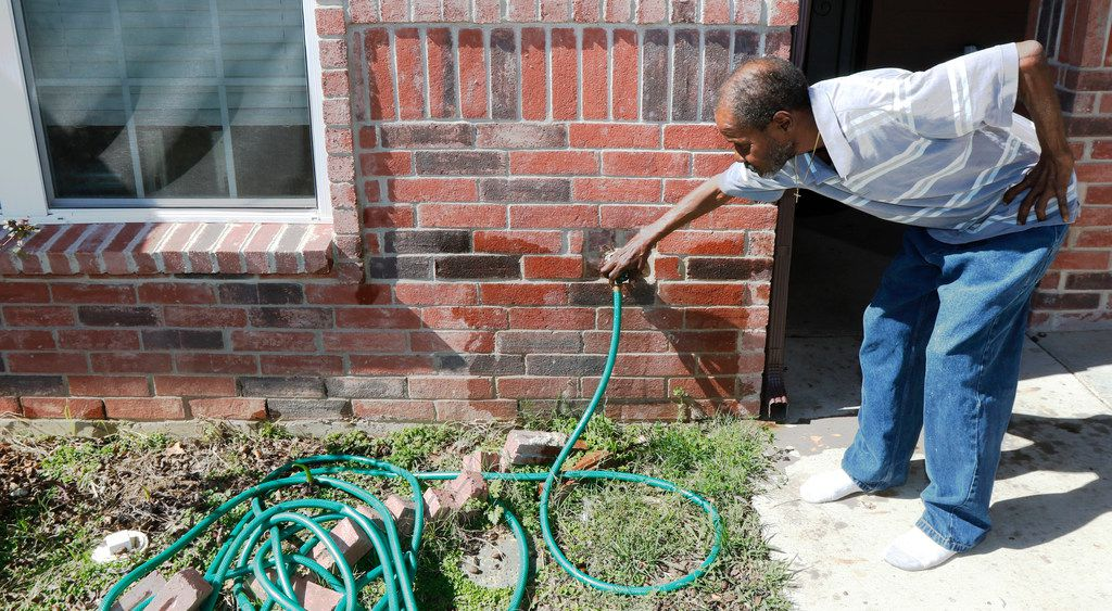 When Raymond Williams turns on his faucet, water runs through the bricks in front of the home where he lives in South Dallas. This house was one of the eight built by Dry Quick Restoration, the construction business run by Kenneth Williams. The two men are not related.