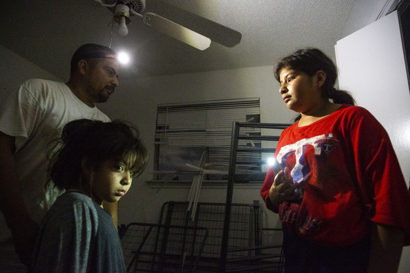 Antonio Gonzalez (left) and his daughters Naia (bottom left), 5, and Giovanna, 14, inspect their home on Glenrio Lane after it sustained significant damage after a tornado hit parts of northern Dallas on Sunday, Oct. 20, 2019.