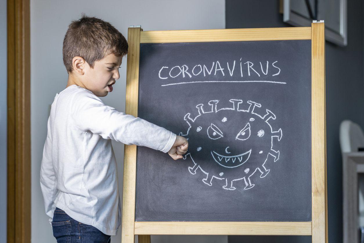 Un niño golpea con su puño un dibujo de la célula de coronavirus.