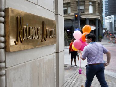 A man with balloons passes by the Neiman Marcus downtown Dallas store on Friday, September 4, 2020. The Dallas-based luxury retailer's reorganization plan was approved by a U.S. Bankruptcy Court on Friday, saving the storied retailer from its unsustainable debt.