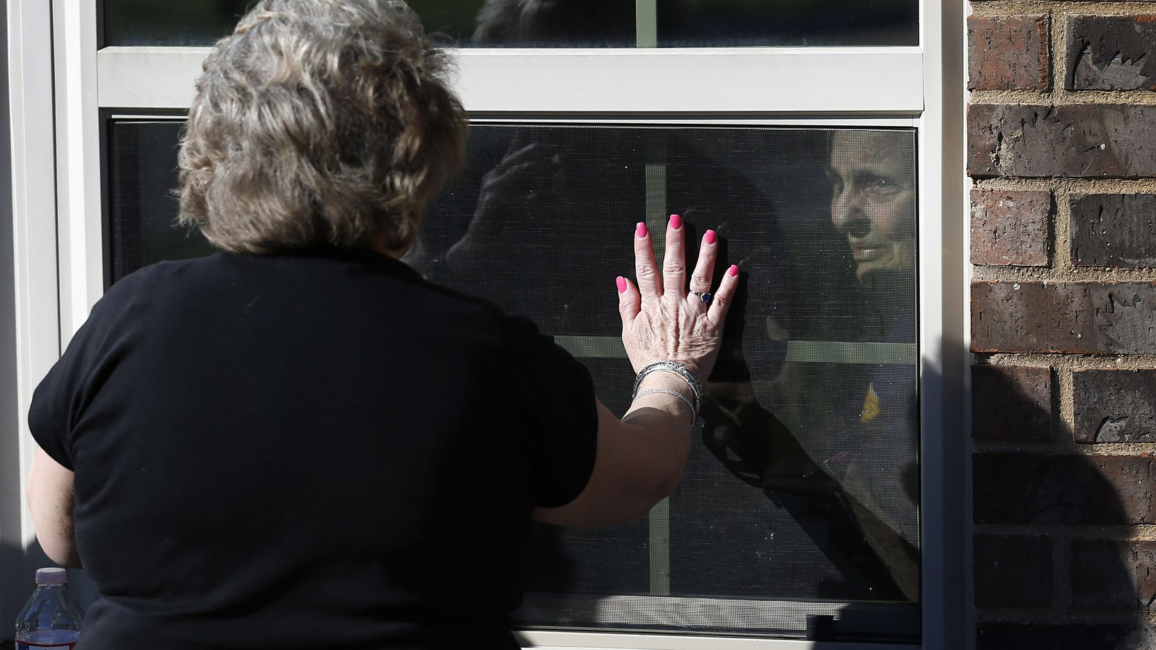 Cindy Goleman waves goodbye to her mother Peggy White from opposites sides of the window at The Pavilion at Creekwood, a healthcare and rehabilitation center in Mansfield, Texas on Tuesday, March 24, 2020. Peggy White had a stroke in late January. Cindy Goleman is one of those people with parents and/or loved ones in nursing homes, hospitals or skilled healthcare facilities who can't visit in person. Goleman visits by looking through the window as she talks to her on the phone.