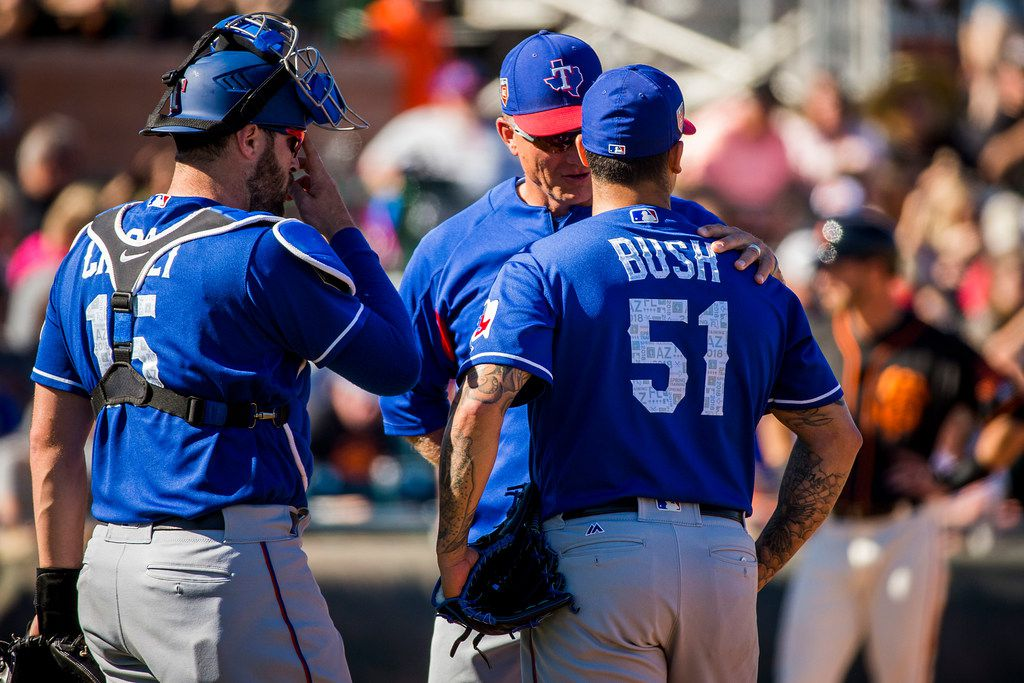 Texas Rangers pitcher Matt Bush gets a visit from manager Jeff Banister and catcher Curt Casali during the sixth inning of a spring training baseball game against the San Francisco Giants on Saturday, March 3, 2018, in Scottsdale, Ariz. (Smiley N. Pool/The Dallas Morning News)