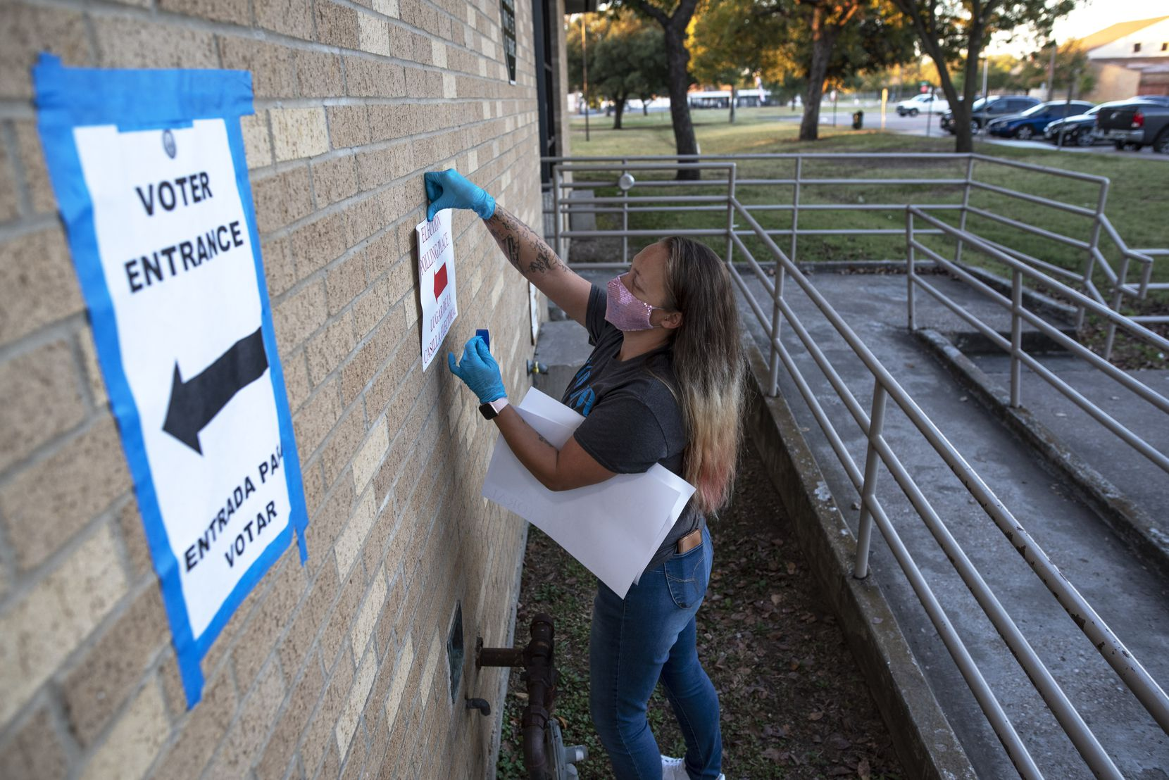 Poll worker Juliana Lee posts entrance signs displaying where to vote outside of the polling location at the Martin Luther King Recreation Center in Dallas.