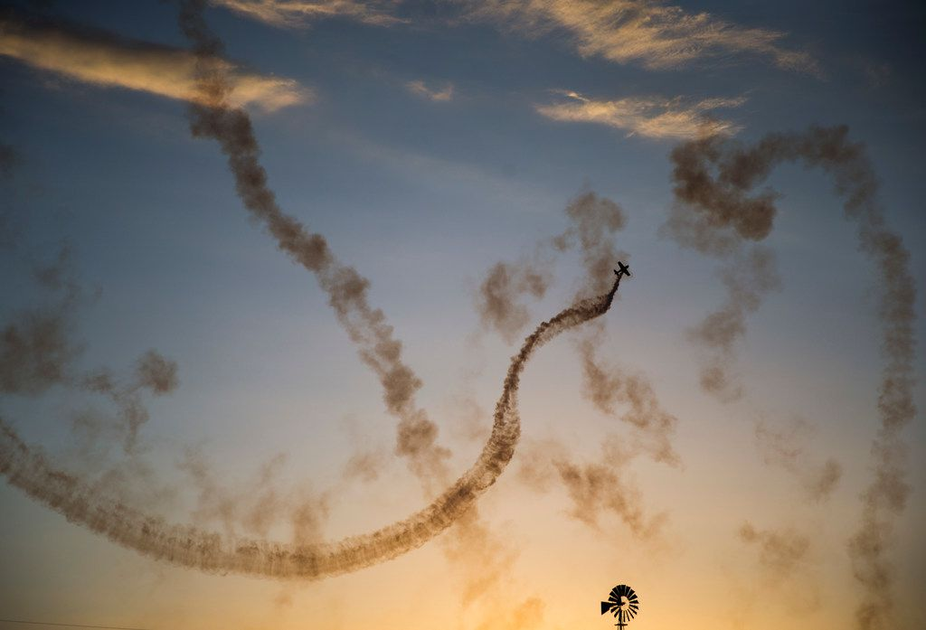 An airplane loops through the sky during an air show during Kaboom Town festivities in Addison, Texas on Tuesday, July 3, 2018. (Ashley Landis/The Dallas Morning News)