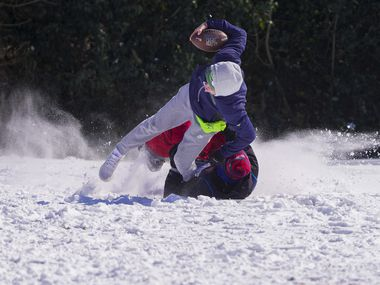 Andre Cavazos is brought down by Wesley Hart as they play football with other friends from J.J. Pearce High School at Prairie Creek Park after winter storm brought snow and freezing temperatures to North Texas on Monday, Feb. 15, 2021, in Richardson.