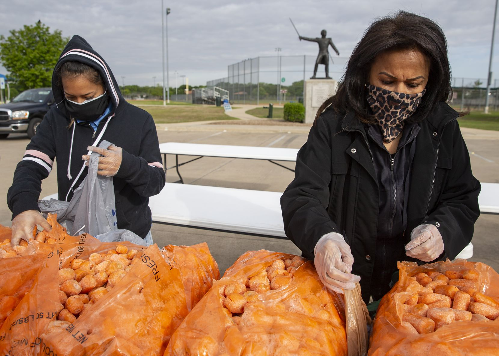 Abby Hernandez, left, and Dolores Dominguez help prepare food to be distributed with the Harvest Food Project Rescue and the Ledbetter Neighborhood Association on April 18, 2020, at Jaycee Zaragoza Park in Dallas.