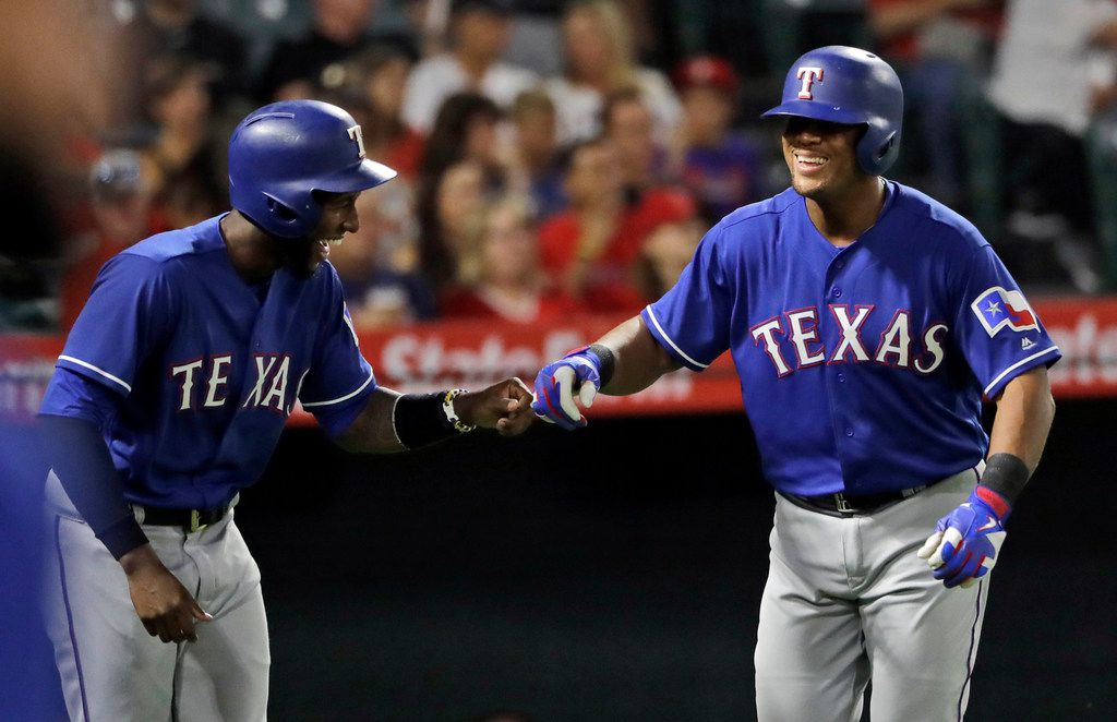 Texas Rangers' Jurickson Profar, left, and Adrian Beltre celebrate as they were both driven in on a double from Joey Gallo during the second inning of a baseball game against the Los Angeles Angels Monday, Sept. 10, 2018, in Anaheim, Calif. (AP Photo/Marcio Jose Sanchez)