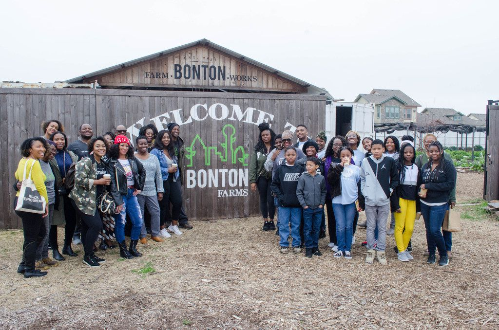 """Attendees of the Soul of Dallas Bus tour pose in front of the """"Welcome To Bonton Farms"""" sign at Bonton Farms in Dallas."""