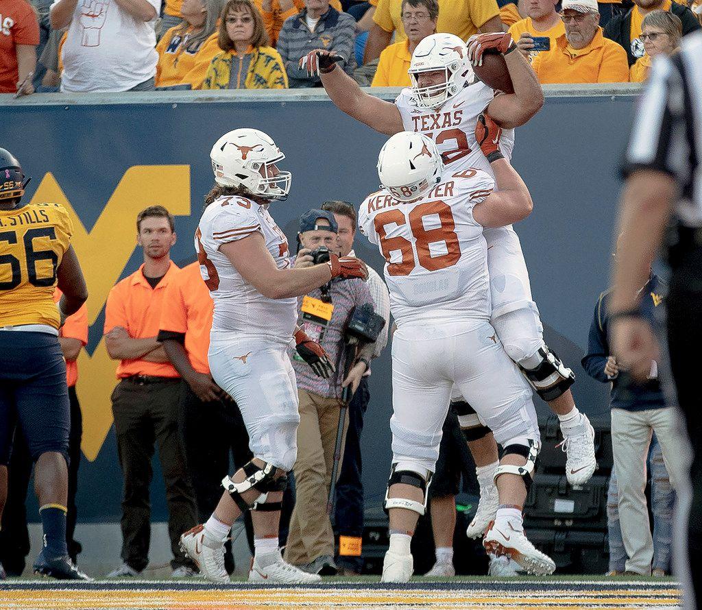 Texas offensive lineman Samuel Cosmi (52) celebrates a touchdown against West Virginia during an NCAA college football game on Saturday, Oct. 5, 2019, in Morgantown, W. Va. (Nick Wagner/Austin American-Statesman via AP)