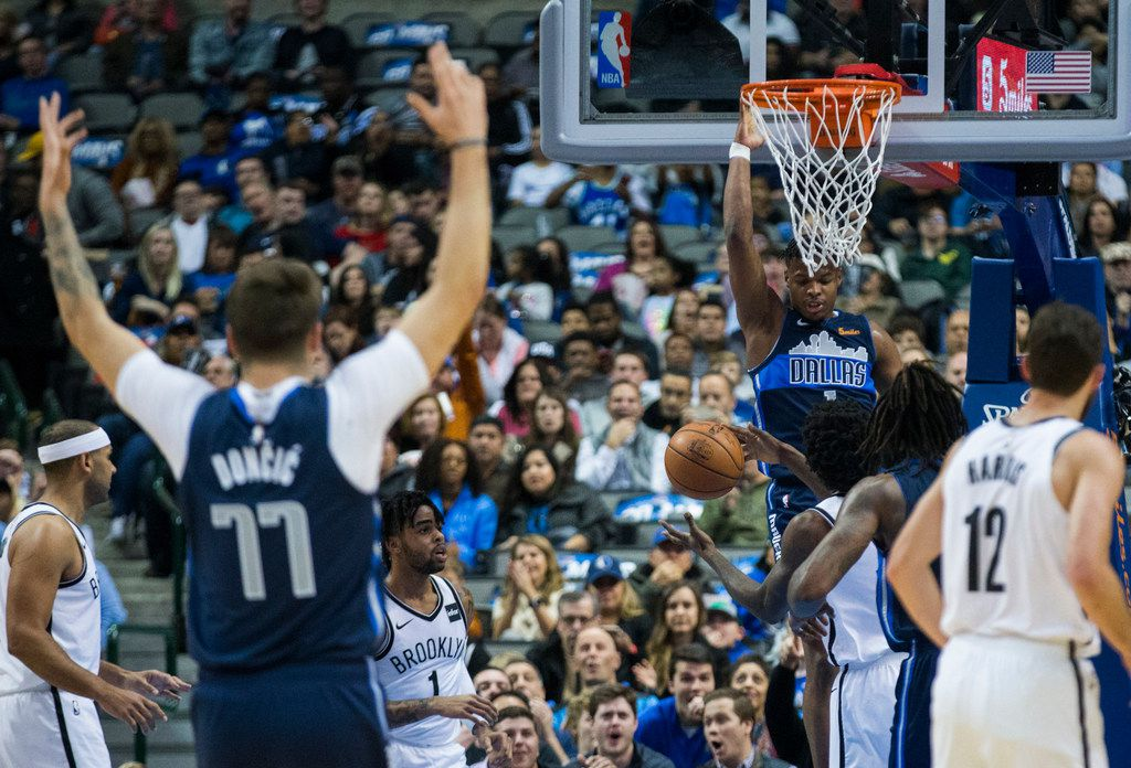 Dallas Mavericks guard Dennis Smith Jr. (1) dunks and forward Luka Doncic (77) reacts during the first quarter of an NBA game between the Dallas Mavericks and the Brooklyn Nets on Wednesday, November 21, 2018 at the American Airlines Center in Dallas. (Ashley Landis/The Dallas Morning News)