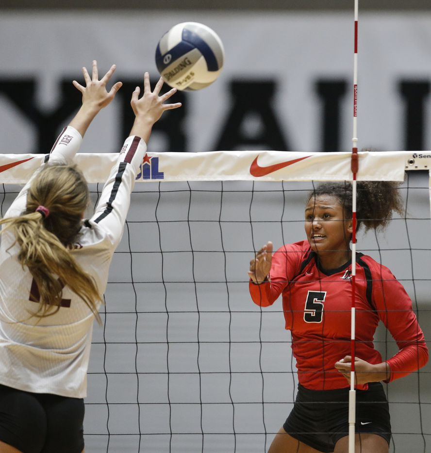 Lovejoy sophomore Cecily Bramschreiber (5) spikes the ball as Dripping Springs junior Avery Kalsu (12) blocks during the Class 5A state semifinal  at the Curtis Culwell Center in Garland, Texas, Friday, November 16, 2018. Lovejoy won in three sets to advance to the finals. (Brandon Wade/Special Contributor)