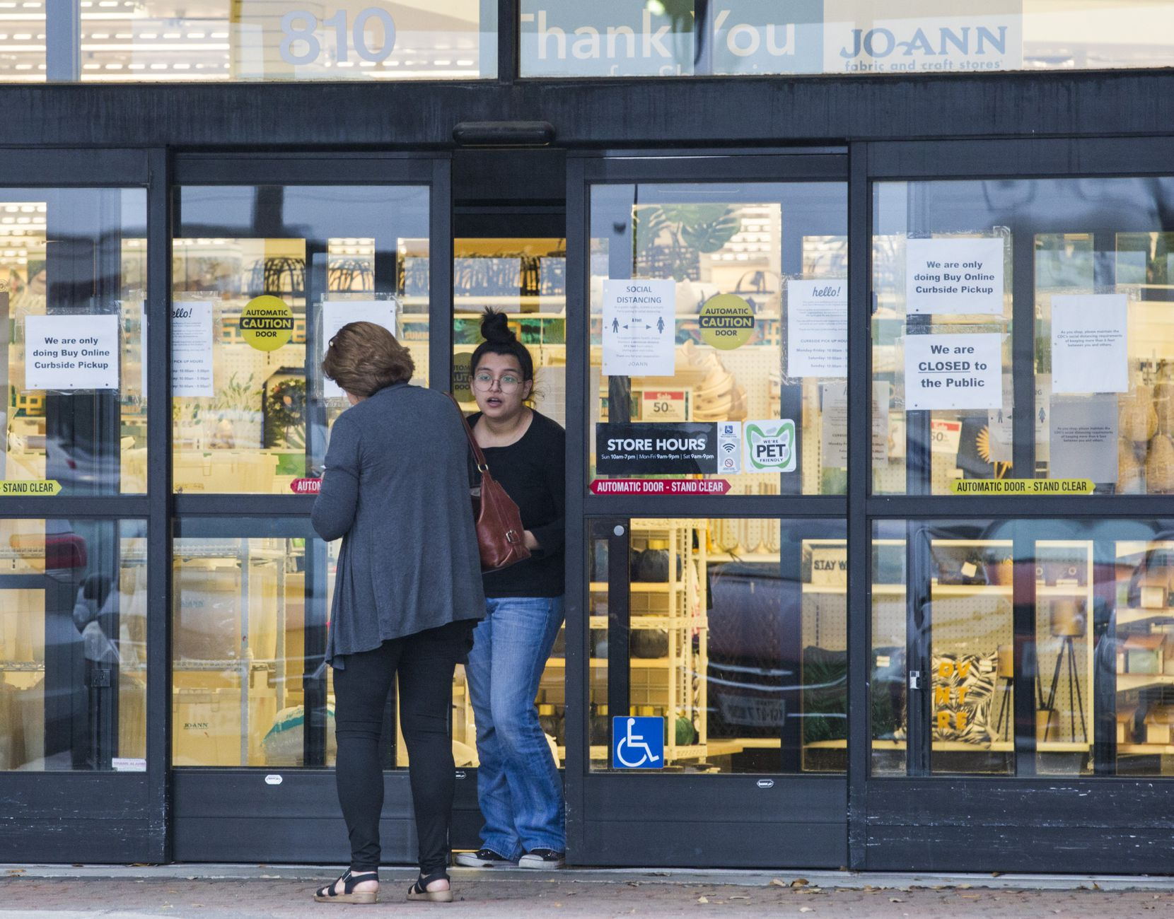 An employee talks to a customer at the front door entrance where signs are posted at Joann fabric store on Friday in Dallas.