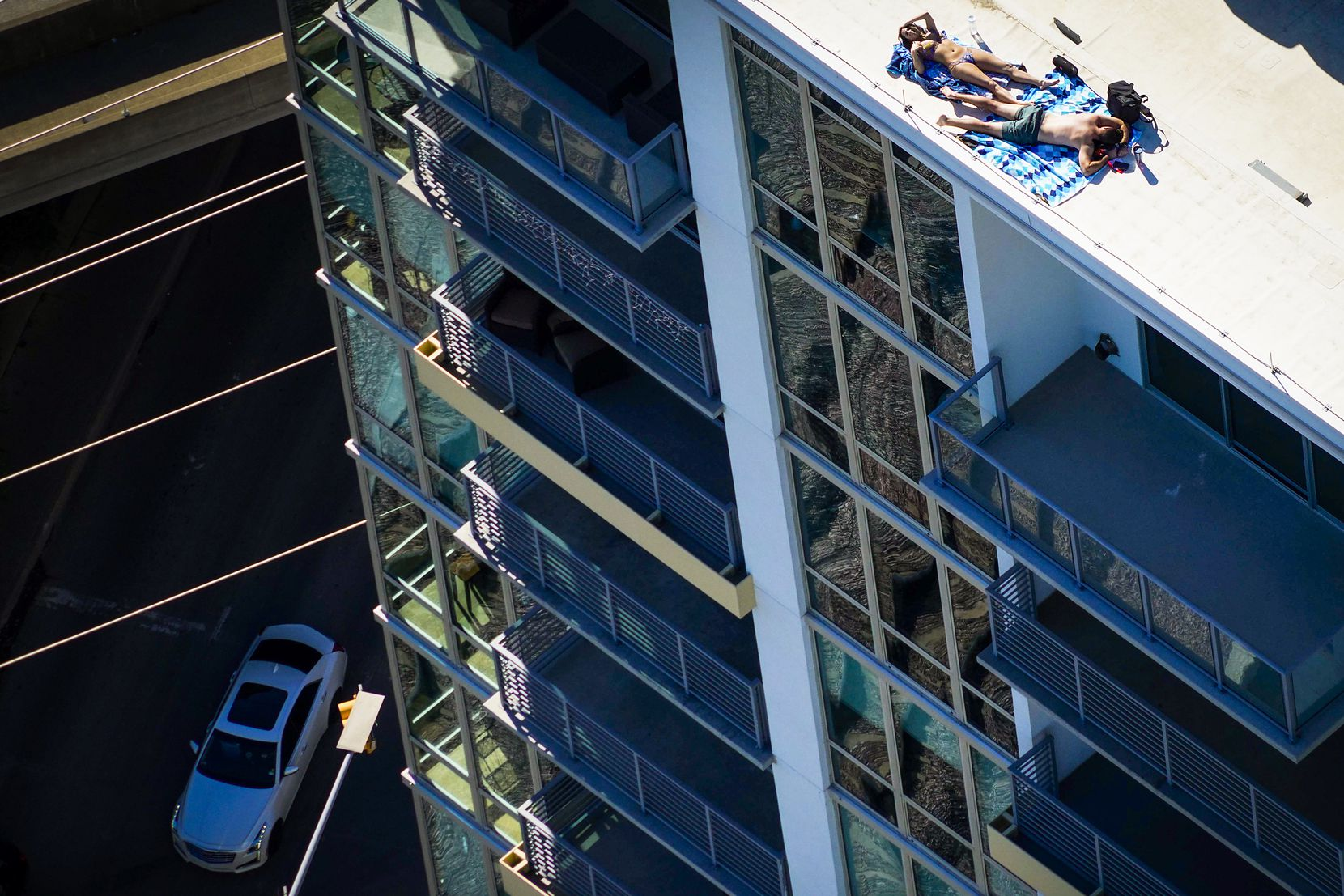 Aerial view of a couple sunbathing on the roof of the The Katy in Victory Park Apartments on March 24, 2020 in Dallas. Dallas County's shelter-in-place order went into effect at 11:59 p.m. the previous day, requiring all people living in Dallas County to stay home, except for essential activities and jobs.