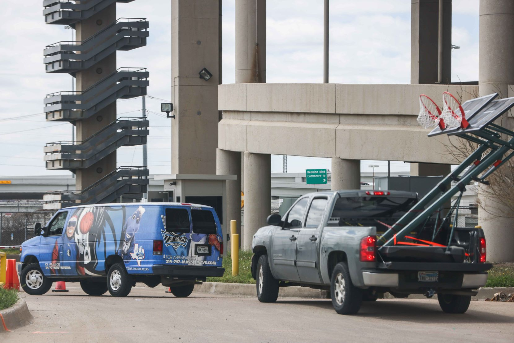 A van with the NBA team Mavericks logo, arrives along with a pickup carrying two basketball hoops to the Kay Bailey Hutchison Convention Center in Dallas on Thursday, March 18, 2021, where 200 unaccompanied immigrant children arrived Wednesday evening. The convention center serves as an emergency intake site to hold teens who have apprehended in increasing numbers at the U.S.-Mexico border.