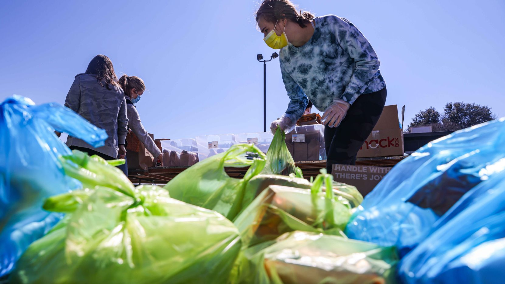 Volunteers distribute food aid to the community at Ledbetter food pantry in Iglesia El Calvario as temperatures start to rise and the snow accumulated after the passage of snowstorm Uri begins to melt in Dallas on Friday, February 19, 2021.