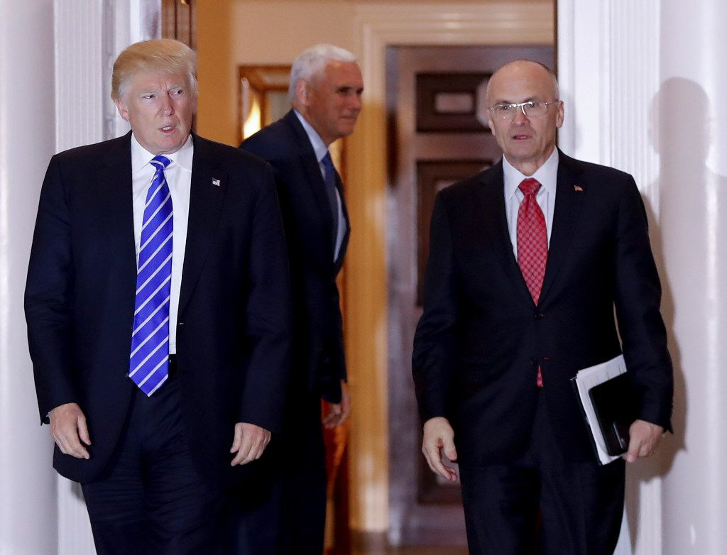 In this Nov. 19, 2016 file photo, President-elect Donald Trump walks Labor Secretary-designate Andy Puzder from Trump National Golf Club Bedminster clubhouse in Bedminster, N.J. Puzder was CEO of a fast food empire that is outsourcing jobs on his watch, a stark contrast with his boss' threats and tweeted slaps at companies that outsource jobs.  (AP Photo/Carolyn Kaster, File)