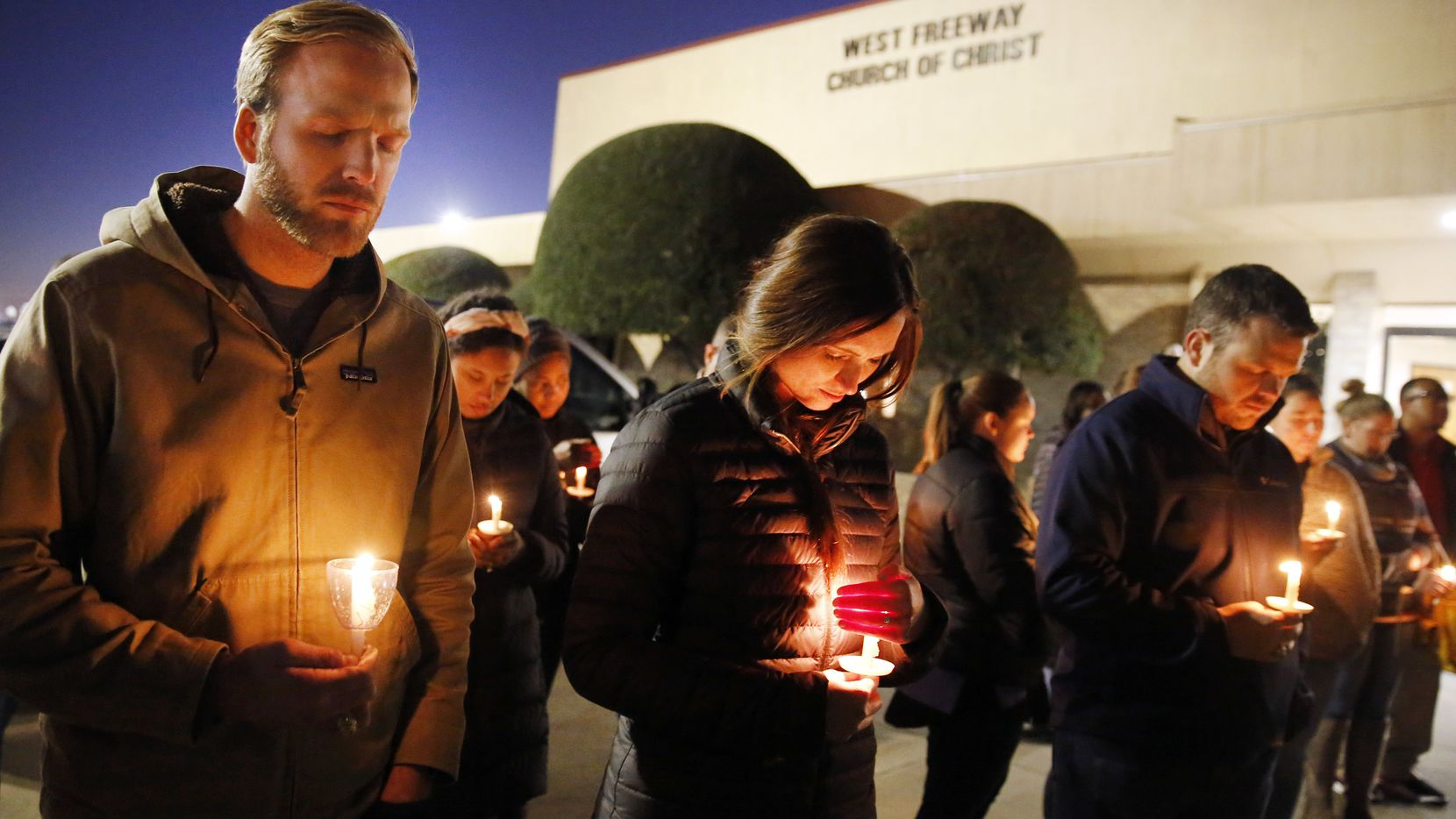 Church and community members, including Matt Pacholczyk (left) and his wife, Faith Pacholczyk, stand outside West Freeway Church of Christ for a candlelight vigil Monday.