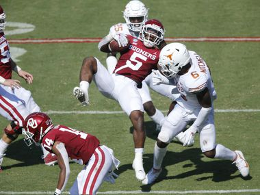 Oklahoma Sooners running back T.J. Pledger  (5) is upended by the Texas Longhorns defense during the Red River Rivalry football game at the Cotton Bowl in Dallas, Saturday, October 10, 2020. (Tom Fox/The Dallas Morning News)