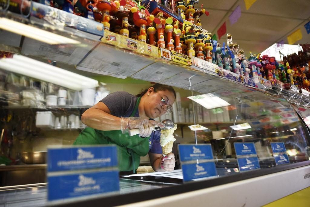 Angélica Rivera (izq.) sirve nieve en un cono para un clinete de La China Poblana, una paletería que opta por vender otras golosinas para sobrevivir durante el invierno. BEN TORRES/AL DÍA