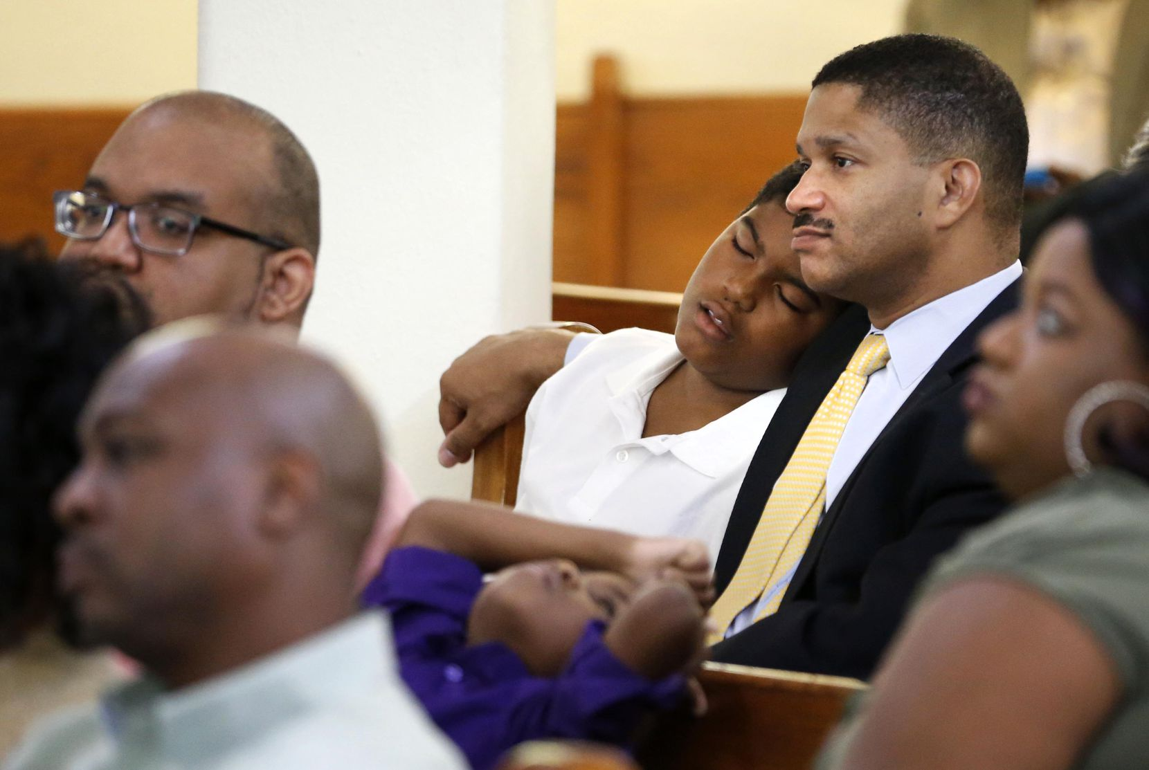 Christopher Waters falls asleep on his father James' shoulder at St. Paul United Methodist Church in Dallas. (Vernon Bryant/Staff Photographer)
