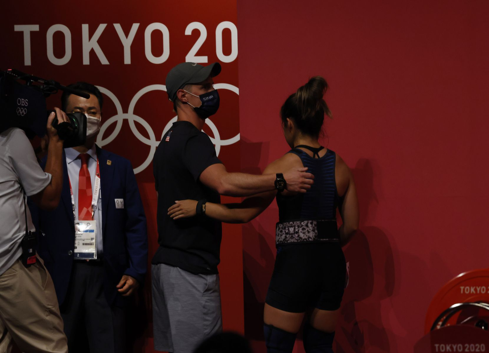 USA's Jourdan Delacruz is consoled by her coach Spencer Arnold after an unsuccessful attempt in lifting 108 kg on her third attempt in the clean and jerk round during the women's 49 kg weightlifting final during the postponed 2020 Tokyo Olympics at Tokyo International Forum on Saturday, July 24, 2021, in Tokyo, Japan. Delacruz received a no-lift on all three attempts of the clean and jerk round. (Vernon Bryant/The Dallas Morning News)